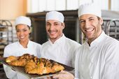 Team of bakers smiling at camera with trays of croissants in the kitchen of the bakery