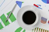 high-angle shot of a cup of coffee on a desk full of charts in the office