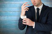 Handsome businessman adjusting his cuffs against wooden planks