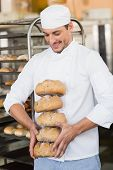 Smiling baker holding fresh loaves in the kitchen of the bakery