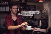 Hipster barista in  plaid shirt adds cinnamon customers cofee.