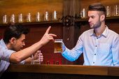 picture of bartender  - Cheerful young bartender is giving a mug with beer to the customer - JPG