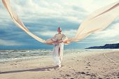 Fashionable Portrait Of Beautiful Model With Very Long Dress Like A Wing. Model Walks At The Beach