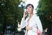 Beautiful Young Business Woman In White Jacket  Talking On Phone On The Street