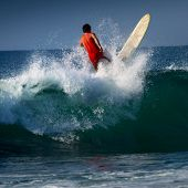 Surfer riding on the wave with long board. Midigama beach, Sri Lanka