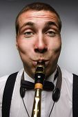 Funny Closeup Portrait Of Blowing Saxophonist. Wide Angle