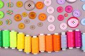 Colorful buttons and sewing threads on wooden background