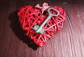 Key on wicker decorative heart on wooden background