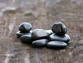 Stack of black sea pebbles on rustic wooden background