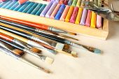 Paintbrushes with colorful chalk pastels in box on fabric background
