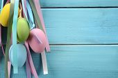 Easter eggs hanging on wood background