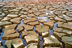 stock photo of water shortage  - little water left on dried and cracked earth - JPG