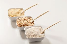 stock photo of rice  - Three types of row rice: white integral and enriched long grain rice. Rice is in three white bowls with three wooden spoons on it ** Note: Shallow depth of field - JPG
