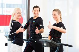 picture of stimulating  - Female coach giving man and woman ems electro muscular stimulation exercise  - JPG