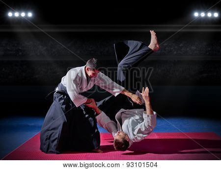 Fight between two martial arts fighters at sports hall poster