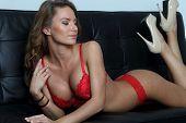 picture of white satin lingerie  - Perfect lingerie model in red on black sofa lying ans posing - JPG