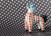 picture of paint horse  - Small ancient painted clay toy horse against black and white Polka Dot background  - JPG