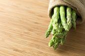 stock photo of bundle  - Bundle of fresh asparagus on wooden chopping board - JPG