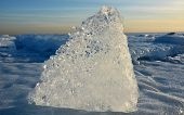 stock photo of crystal clear  - Crystal clear ice at sunset at frozen sea - JPG