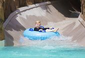 pic of inflatable slide  - Happy little boy enjoying a wet ride down a water slide - JPG