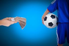 stock photo of corruption  - Back view of youth soccer player in blue uniform and little kid holding a ball and hand holding stacks of banknotes on blue background concept about corruption or bribery of match of soccer - JPG