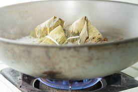 foto of chinese wok  - Zongzi boiling in a wok - JPG