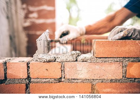 Bricklayer Worker Installing Brick Masonry On Exterior Wall With Trowel Putty Knife