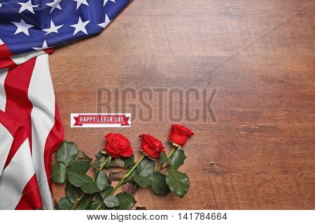 Roses and American flag on a wooden background. Labor day concept