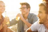 Постер, плакат: Young man and woman drinking beer while sitting on beach at sunset Group of guys and girls out on a