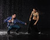 pic of dancing rain  - Young couple dancing in water under rain on a black background - JPG