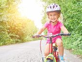 Happy Child Riding A Bike In Outdoor. poster