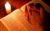 Bible by candle light with hands folded