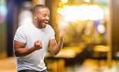 African american man with beard happy and excited celebrating victory expressing big success, power, poster