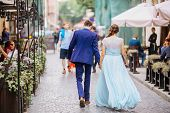 Portrait The Groom In Wedding Suit And The Bride In  Dress Walking Back Near Old Building, Old House poster