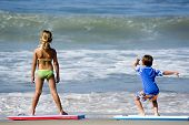 Two Kids Playing With Body Boards On The Beach