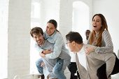 Cheerful Young Businesspeople Laughing And Having Funny Piggyback Ride, Happy Employees Enjoying Pla poster
