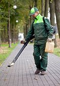 Landscaper cleaning the track using Leaf Blower