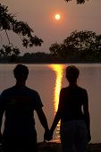 Young Couple Lookiing At Sunset