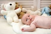 Infant With Blue Eyes And Surprised Face On Light Blanket With Toys On Background, Defocused. Baby B poster