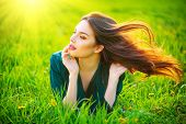 Beauty woman lying on the field with healthy long flying hair. Beautiful brunette Girl lying on the  poster
