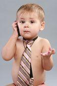 Little Boy In Tie Speaks On A Cell Phone
