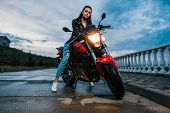 Biker Girl In A Leather Jacket On A Black And Red Color Motorcycle poster