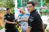 Male ambulance professional with happy senior woman on stretcher