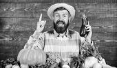 Man With Beard Wooden Background. Farmer With Organic Vegetables. Gardening And Farming Systems Pres poster