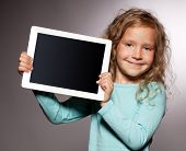Happy child with tablet computer. Kid showing