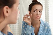 Teen Girl Applying Acne Healing Patch Near Mirror In Bathroom poster
