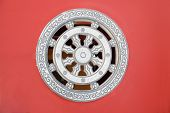 Stone rosette relief - window made of decorated stone relief, ornaments and relief on the red wall f poster