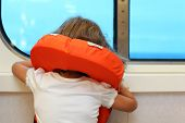 Back of little girl dressed in life jacket, which stands near window in cabin of ship and looks into