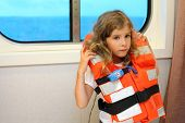 Sad little girl dressed in life jacket stands near window in cabin of ship