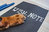 Ginger Dog Paw On Wish Note At The Table. Wish List Or New Year Resolution Concept. poster